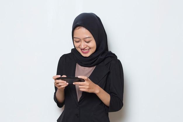 彼女のスマートフォンでゲームをプレイすることに興奮しているアジアのイスラム教徒の女性