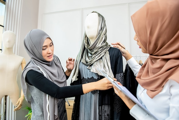 Asian muslim woman fashion designers workingn tailor shop
