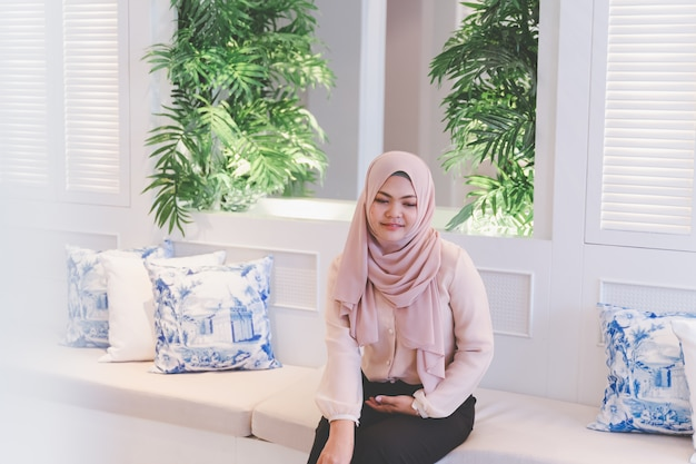 Asian muslim woman having a good day sitting on the white table in the beautiful bright living with green plants