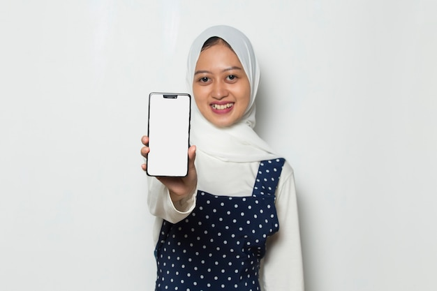 Asian muslim woman in hijab demonstrating mobile cell phone portrait of smiling girl