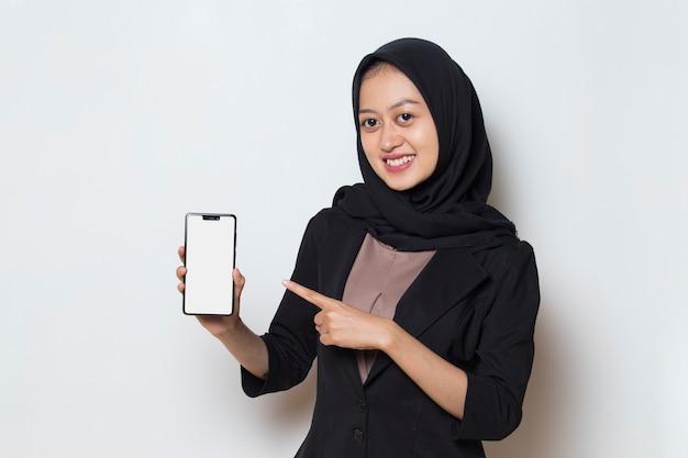 Asian muslim woman in hijab demonstrating mobile phone