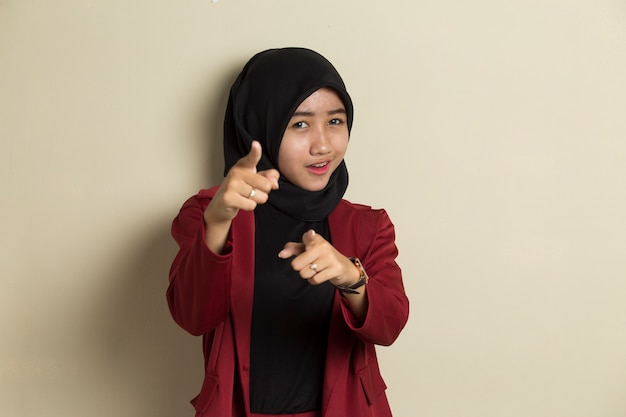 Asian muslim woman in hijab smiling while pointing forward