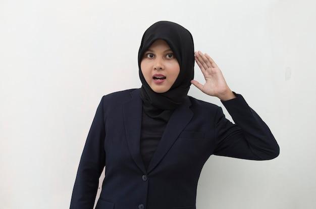 아시아 이슬람 여자는 그녀의 귀 근처에 그녀의 손을 잡고 듣고