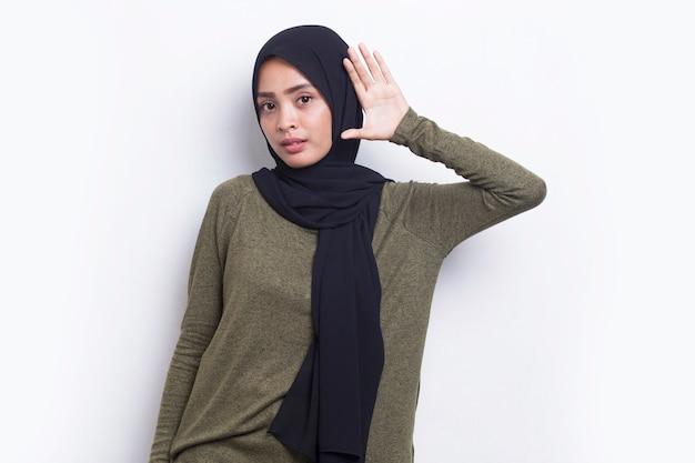 아시아 이슬람 여성이 귀에 손을 대고 듣고 있다