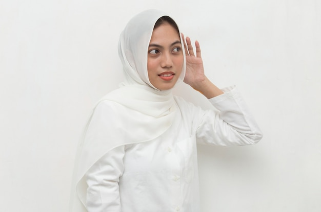 Asian muslim woman hold her hand near her ear and listening