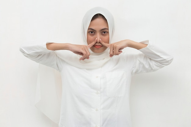 Asian muslim woman holding her nose because of a bad smell