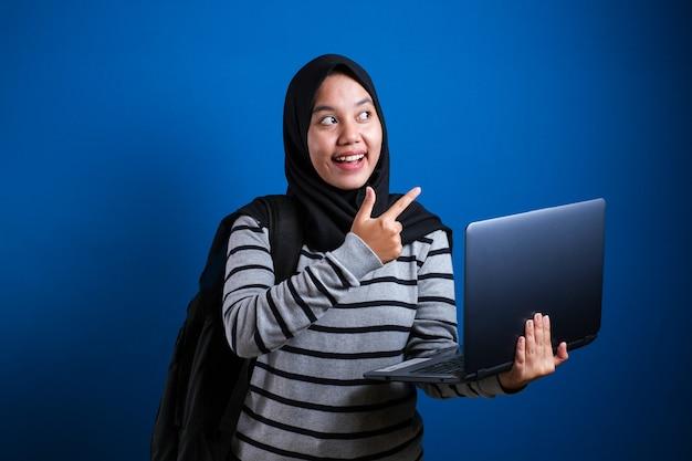 노트북을 들고 옆을 가리키는 아시아 이슬람 여성, 파란색 배경에 대해 뭔가 제시