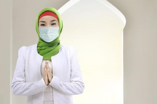 ベールと祈るインフルエンザマスクを身に着けているアジアのイスラム教徒の女性