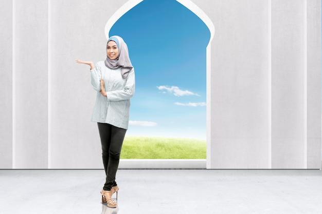 모스크에 뭔가 보여주는 베일에 아시아 무슬림 여성. 복사 공간을위한 빈 영역