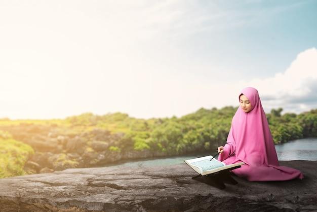 베일에 아시아 무슬림 여성이 앉아 야외에서 꾸란을 읽고