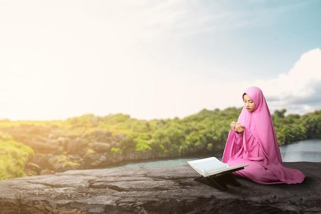 베일에 아시아 무슬림 여성이 손을 들고 야외에서기도하는 동안 앉아