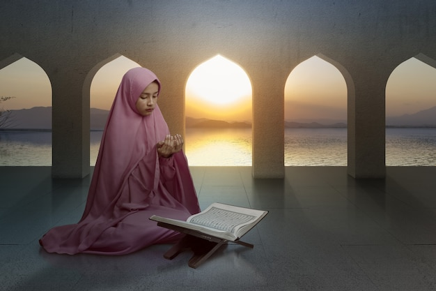 手を上げてモスクで祈っている間座っているベールのアジアのイスラム教徒の女性