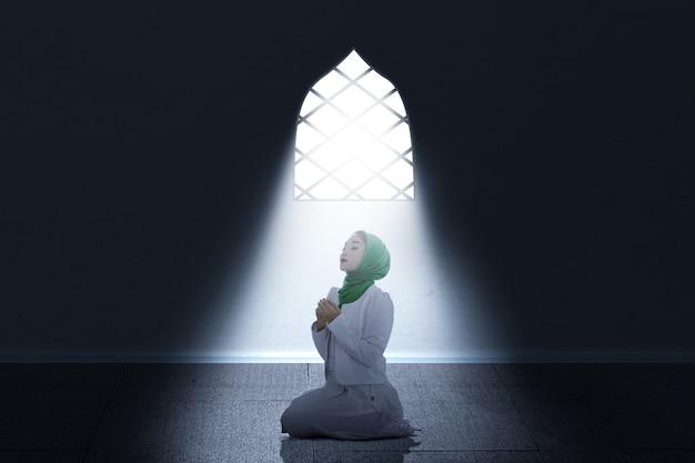 베일에 아시아 무슬림 여성이 앉아있는 동안 손을 들고 방 안에서기도합니다.