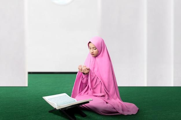 베일에 아시아 무슬림 여성이 손을 들고 모스크에기도하는 동안 앉아