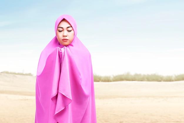 Азиатская мусульманская женщина в хиджабе стоит, подняв руки и молясь на дюне