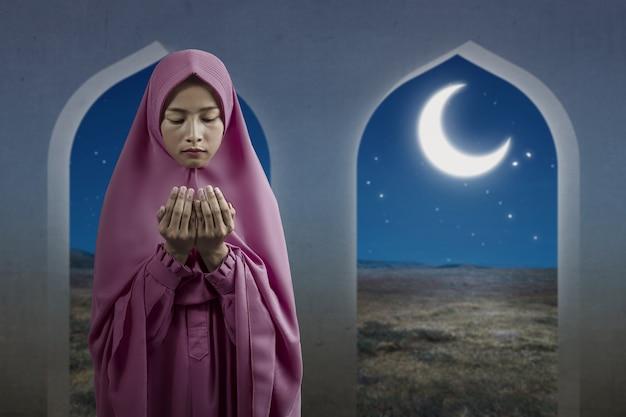 베일에 아시아 무슬림 여성이 서있는 동안 손을 들고 모스크에서기도합니다.
