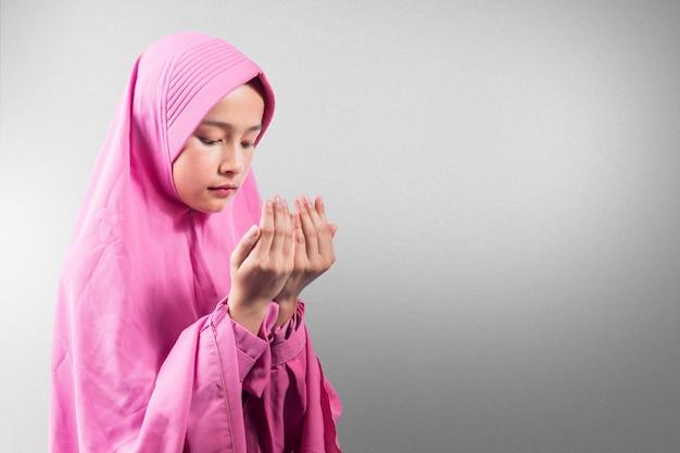 手を上げて霧の背景で祈っている間立っているベールのアジアのイスラム教徒の女性