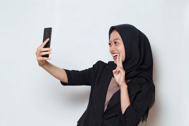 自撮りを作る携帯電話とヒジャーブのアジアのイスラム教徒の女性