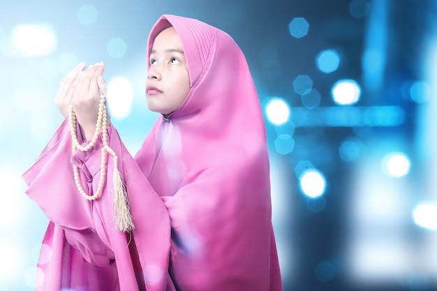 ぼやけた明るい背景で彼女の手に数珠で祈るベールのアジアのイスラム教徒の女性