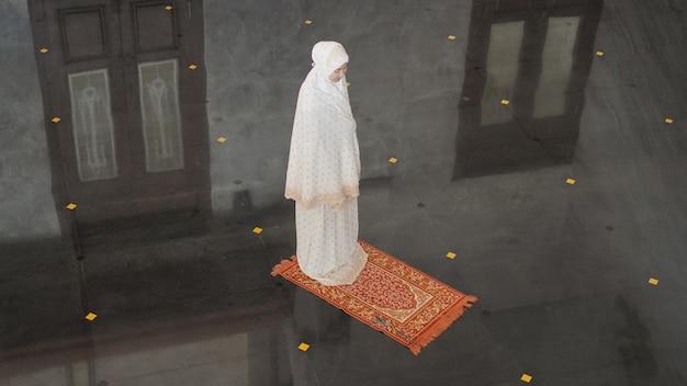 モスクでイマームなしで一人で祈るアジアのイスラム教徒の女性