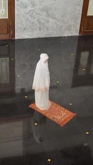 Азиатская мусульманка молится одна без имама в мечети