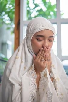 Азиатская мусульманская женщина молится
