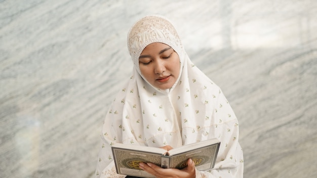 Asian muslim woman reading the quran in the mosque