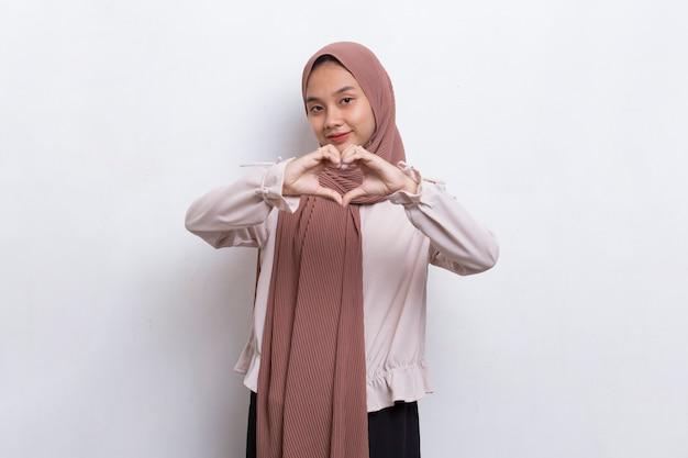 白い背景で隔離のハートサイン愛を示すアジアのイスラム教徒の女性
