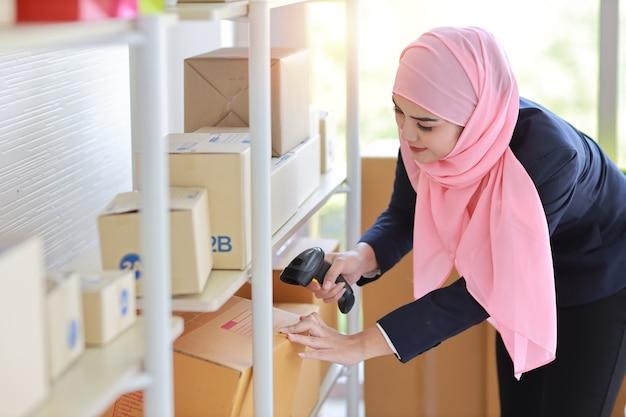 Азиатская мусульманская женщина стоя и держа сканер с доставкой коробки пакета.