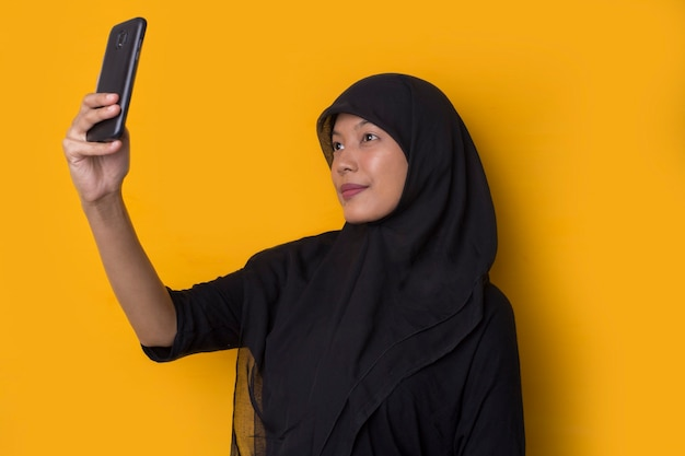 Asian muslim woman taking a selfie on yellow background