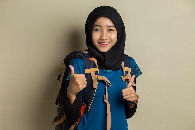 Азиатская мусульманская женщина-путешественница в хиджабе с жестом знак ок