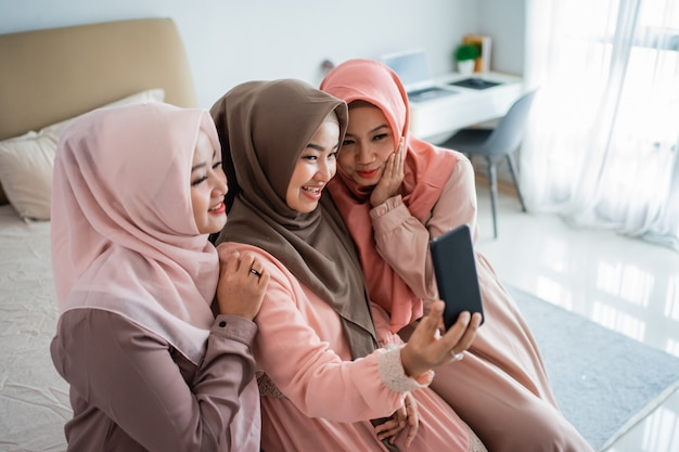 Азиатская мусульманская женщина, используя мобильный телефон, сидя на кровати