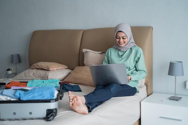 オンラインアプリケーションを介してラップトップを使用して出発スケジュールを探しているアジアのイスラム教徒の女性