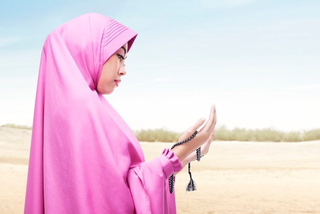 Asian muslim woman in veil praying with prayer beads on her hands on the dune