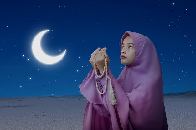 Asian muslim woman in veil praying with prayer beads on her hands with the night scene background