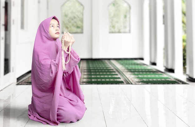 Asian muslim woman in veil sitting and praying with prayer beads on her hands