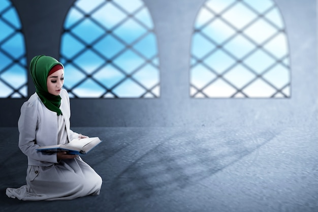 Asian muslim woman in a veil sitting and reading the quran on the mosque