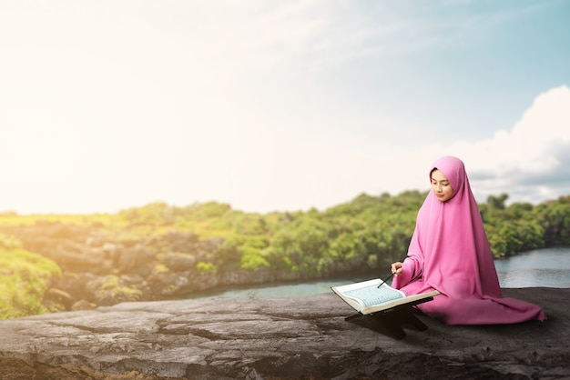 Asian muslim woman in a veil sitting and reading the quran at outdoor