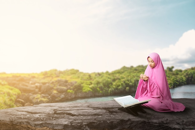 Asian muslim woman in a veil sitting while raised hands and praying at outdoor