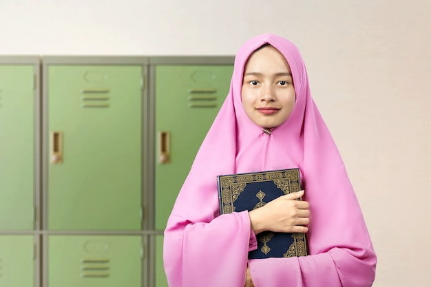 Asian muslim woman in a veil standing and holding the quran