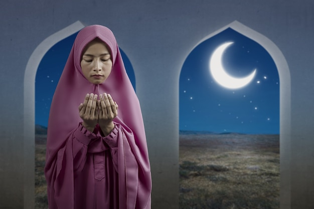 Asian muslim woman in a veil standing while raised hands and praying on the mosque