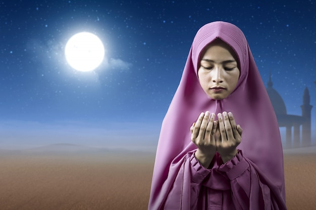 Asian muslim woman in a veil standing while raised hands and praying