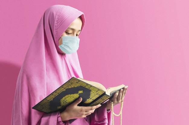 Asian muslim woman in a veil and wearing flu mask holding prayer beads and reading the quran