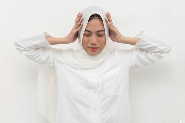 Asian muslim woman wearing hijab covering her ears
