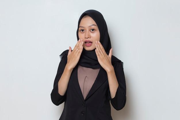 Азиатская мусульманка в хиджабе потрясена, прикрывая рот руками за ошибку секретной концепции
