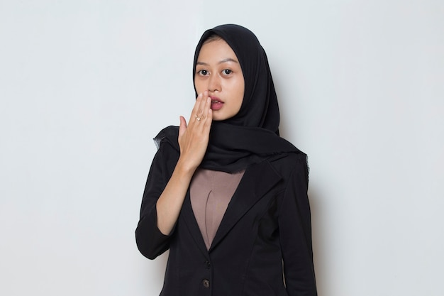 Asian muslim woman wearing hijab shocked covering mouth with hands for mistake secret concept