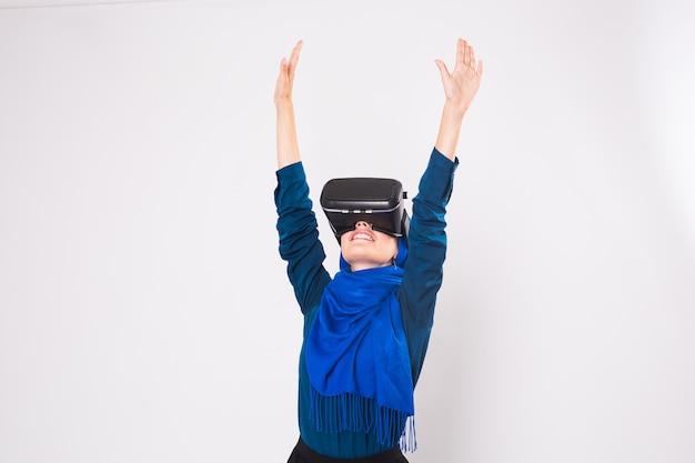 Азиатская мусульманская женщина в хиджабе с помощью очков виртуальной реальности vr на белом фоне.