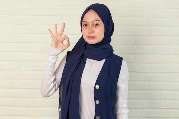 확인 표시 제스처와 hijab를 입고 아시아 무슬림 여성
