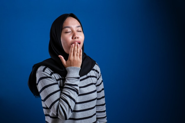 Asian muslim woman wearing hijab yawning tired, dizzy expression. close up head and shoulders over blue background