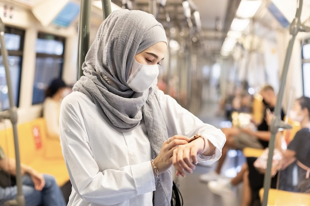 Asian muslim woman wearing medical face mask for prevent dust and infection virus and looking smartwatch in skytrain transit system public.
